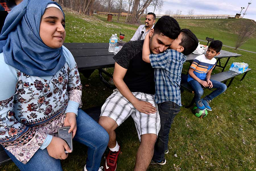 Yasser, 5, tells big brother Hussain, 18, a secret as sister Rokaia, 12, left, and other family and friends gather for a picnic at Hawk Island in Lansing.