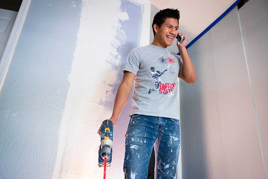 Diego Ixcotoyac-Us, a 19-year-old Guatemalan refugee, speaks to his brother on the phone while working at his side job remodeling a rental property in the Lansing area. He graduated from Sexton High school and looks forward to applying for citizenship in 2019.