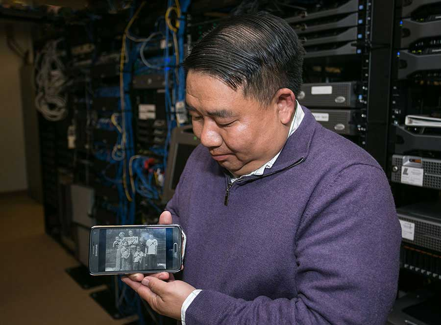 Tou holds an old photograph of his family, each member checked off and accounted for as they prepared to leave a Thai refugee camp for resettlement in Michigan.